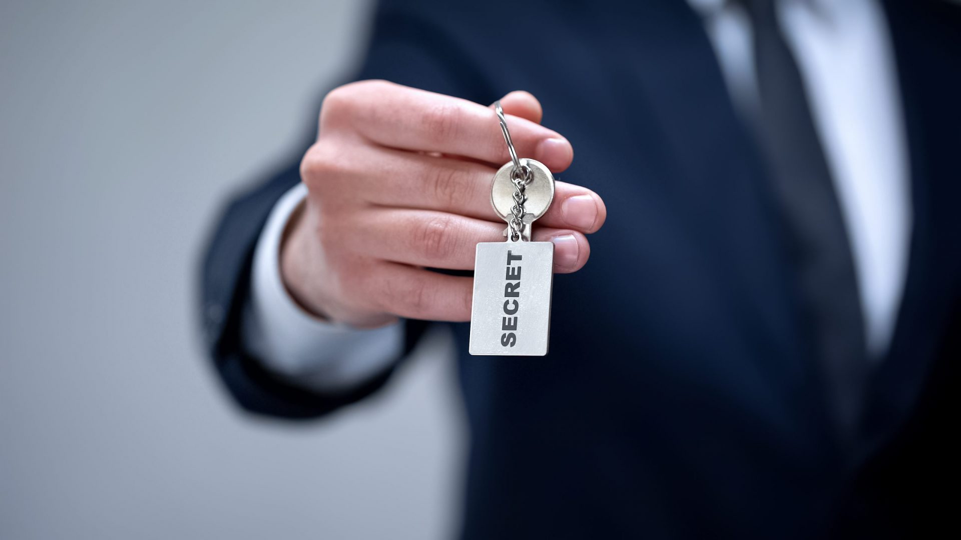 Secret word on keychain in businessman hand, access to confidential information