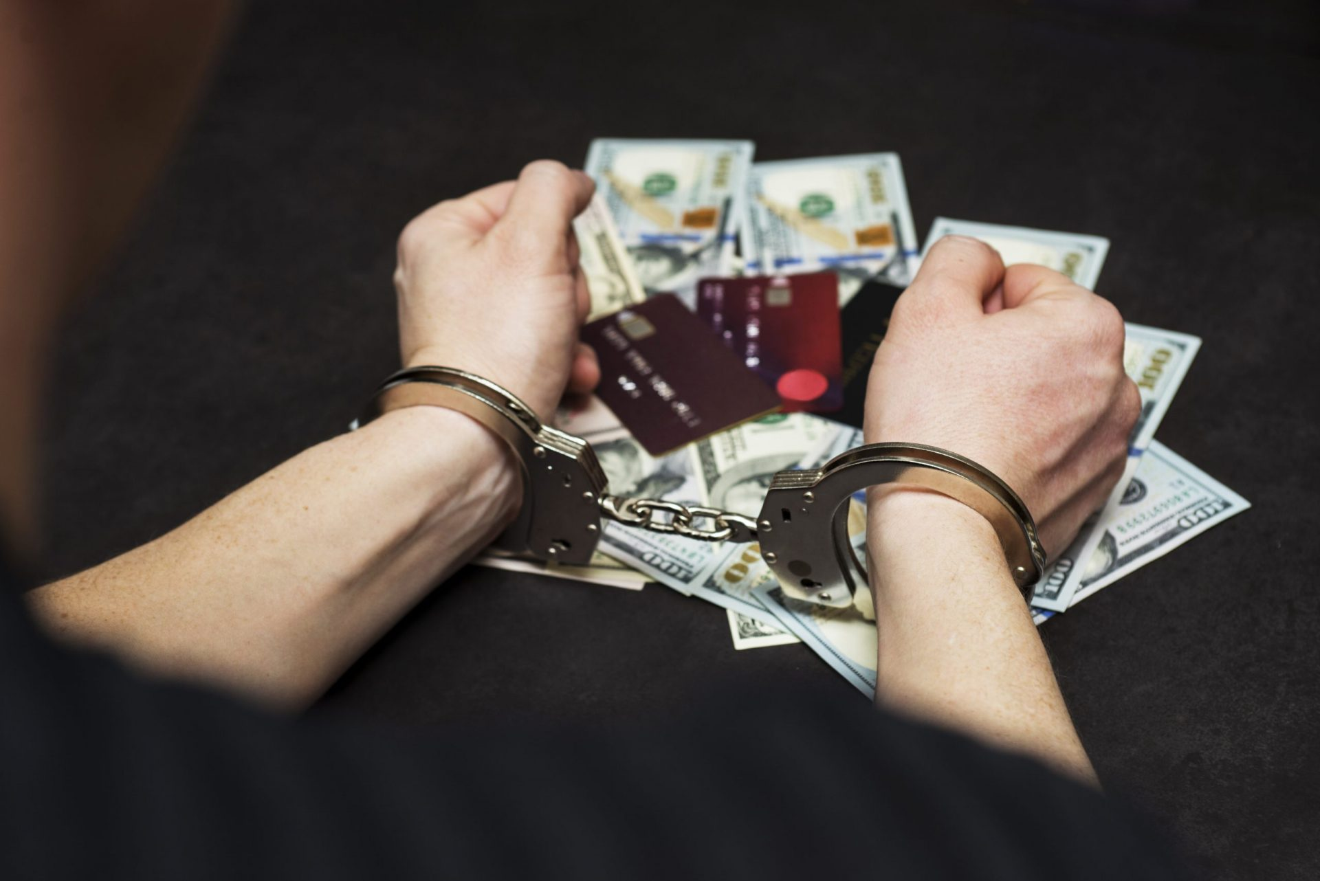 Hands of a fraudster with handcuffs on a background of us dollars and credit cards. Fraud, cyber crime concept